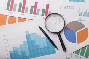 Magnifying glass and documents with analytics data lying on wood table photo