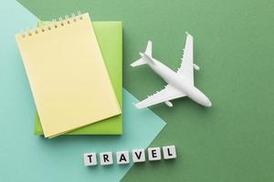 concepto de viaje con avión blanco y cuadernos foto