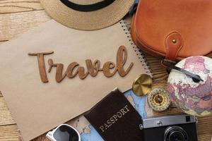 Travel items on wooden background top view photo