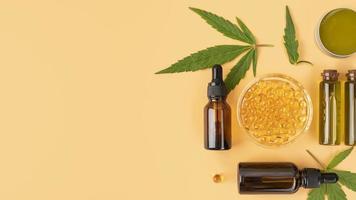 Vista superior surtido de botellas de aceite de cannabis natural con hojas de cannabis foto
