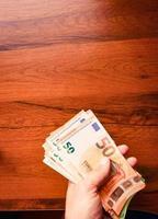 mano sostiene la pila de cincuenta billetes en euros Fondo de mesa de madera. sueldos y salario mínimo en unión europea. foto