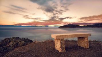Stone bench at sunset. Beautiful sunset over the Aegean sea, Peninsula Kassandra, Halkidiki, Greece. On the horizon we see peninsula Sithonia and peninsula Athos behind. photo