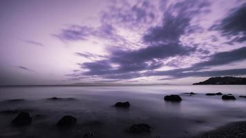 Landscape of sand and rocky shore. Beautiful cloudy seascape at sunset and blurred motion water, Kassandra, Greece. photo