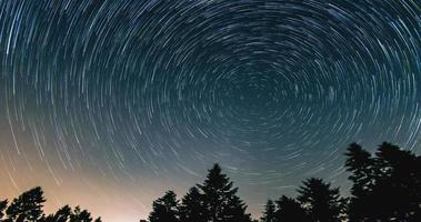 Star trails over the night sky - comet mode, Time lapse of star trail, pine trees in the foreground, Avala, Belgrade, Serbia. The night sky is astronomically accurate. photo