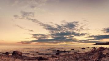 Landscape of sand and rocky shore. Beautiful cloudy seascape at sunset, Kassandra, Greece. photo