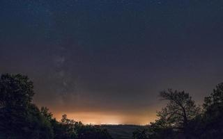 galaxia de la vía láctea sobre la enorme ciudad. galaxia de la vía láctea sobre belgrado, vista desde la montaña avala, serbia, europa. el cielo nocturno es astronómicamente exacto. foto