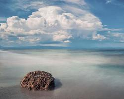 Landscape of sand and rocky shore. Beautiful cloudy seascape at sunset and blurred motion water. photo