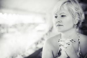 Monochromatic portrait of the blonde woman who pose and looking aside and waiting for her dinner in the restaurant. Black and white photo of the blonde woman in the caffe pizzeria.