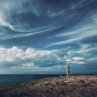 Blonde woman standing on top of the hill and looking over the sea. Beautiful sky over Aegean sea, peninsula Kassandra, Greece. photo