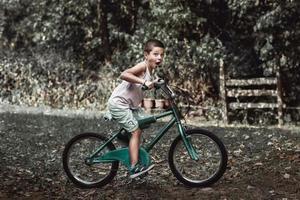un niño con cara divertida montando su vieja bicicleta rústica. un niño monta su vieja bicicleta en el patio trasero y hace una mueca. foto
