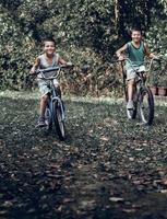 dos jóvenes montando viejas bicicletas rústicas. dos niños monta una bicicleta vieja en el patio trasero y mirando a la cámara. foto