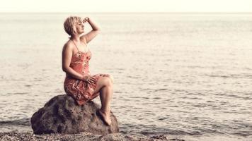 Blonde woman in purple dress sitting on the huge rock next to the sea, looking at the sunset and waiting for something or somebody. photo