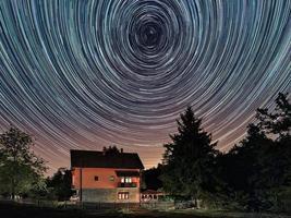 Estelas de estrellas sobre la casa. edificio residencial y los rastros de estrellas en el cielo. el cielo nocturno es astronómicamente exacto. foto