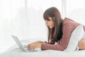 mujeres asiáticas, trabajando, con, computador portatil, cama foto