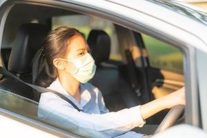 Hermosa mujer asiática conduciendo un automóvil con mascarilla saliendo mantenerse saludable protegiendo del coronavirus virus covid-19 foto