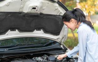 Young woman standing near broken down car with popped up hood having trouble with her vehicle photo