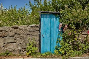 Stone wall and blue door on Bornholm island in Svaneke, Denmark photo