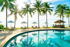 Beautiful luxury umbrella and chair around outdoor swimming pool in hotel and resort with coconut palm tree on blue sky photo