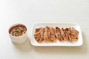 Grilled pork neck or charcoal-boiled pork neck with Thai spicy dipping sauce photo