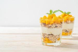 Fresh mango yogurt with granola in glass - healthy food style photo