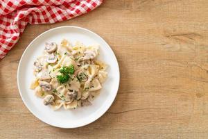 Farfalle pasta with mushroom white cream sauce - Italian food style photo