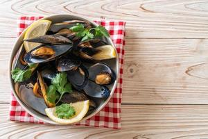 Fresh mussels with herbs in a bowl with lemon photo