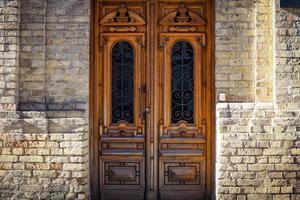 Gran puerta antigua de madera marrón en edificio de pared de ladrillo foto