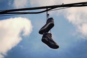 Two dirty old sneakers hanging on wires in blue sky with clouds photo