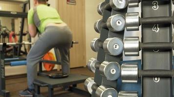 Man Does Squats with A Weight Disc video