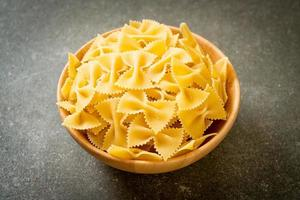 Dry uncooked farfalle pasta in wooden bowl photo