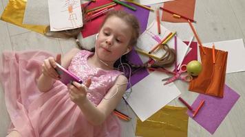niña tendida en el suelo escuchando música en el teléfono video