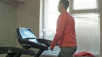 Strong young man on treadmill In gym video