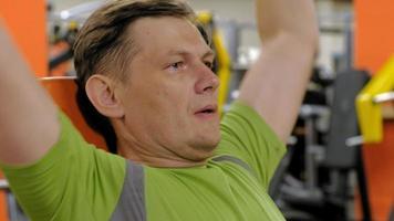 um homem fazendo supino com halteres sentado com as mãos retas em uma academia de ginástica video
