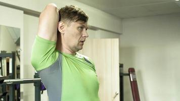 l'uomo in palestra fitness e sport heman allunga le braccia in palestra. preparazione per la formazione. stile di vita fitness stile di vita sano video
