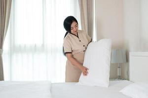 Young beautiful Asian maid arranging a pillow on the bed in a hotel room. photo