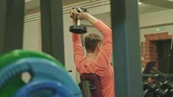 Man doing développé couché avec haltères en studio de remise en forme video