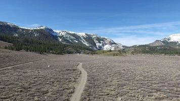 photo aérienne d'un sentier de randonnée dans une prairie en contrebas d'une montagne pittoresque. video