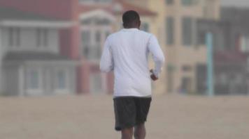 een jonge man die naar muziek luistert terwijl hij op het strand rent. video