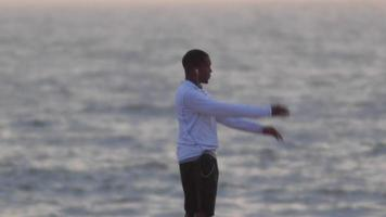 un corredor joven que se extiende en la playa al atardecer. video