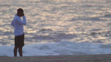 un corredor joven hablando por su teléfono celular en la playa. video