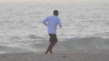 een jonge man loopt door de oceaan op het strand. video