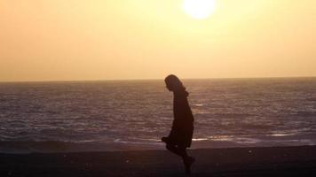 silhuett av en kvinna som går på stranden vid solnedgången. video