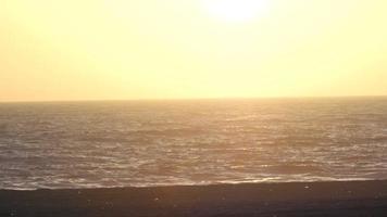 een jonge man loopt op het strand bij zonsondergang. video