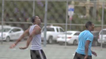 dois jovens jogando basquete um contra um juntos em uma quadra ao ar livre cercada por uma cerca de arame. video