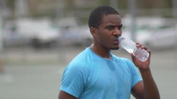 jogadores de basquete bebendo água em uma quadra de basquete ao ar livre. video