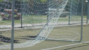Soccer goal net blowing in the wind on a turf playing field. video