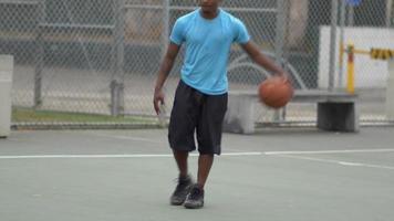 jovem jogador de basquete driblando uma bola de basquete em uma quadra ao ar livre. video