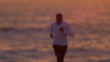 un joven corriendo en la playa al atardecer. video