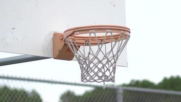 Basketball going into outdoor basketball hoop. video