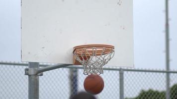um jovem atirando em uma quadra de basquete ao ar livre. video